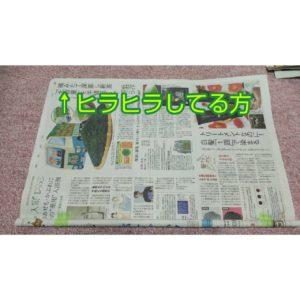 棒状に丸められてテープで留められた新聞紙と新しい新聞紙
