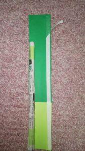 切られた黄緑と緑の画用紙に両面テープを貼り、新聞紙の棒をくっつけたところ