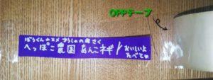 切った紫色の折り紙に文字を書いた紙にOPPテープを貼る