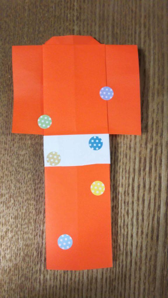オレンジの折り紙で作った紙衣にシールが貼られている