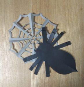 灰色の折り紙で作ったクモの巣と黒い折り紙で作ったクモ