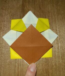 黄色い折り紙で作った折り紙の花と茶色い折り紙で作ったひまわりの中心