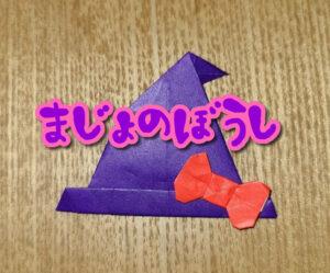 紫の折り紙で作った魔女の帽子に赤いリボンがついている
